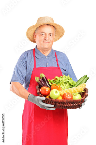 Mature farmer man holding a basket with fresh vegetables