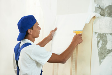 painter worker peeling off wallpaper