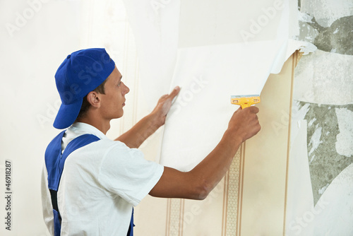painter worker peeling off wallpaper
