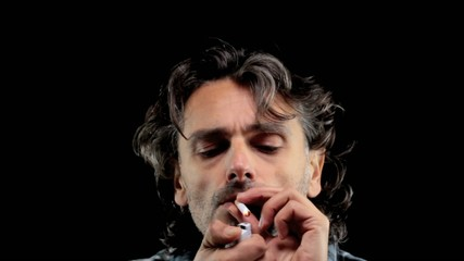front view of a man lighting a cigarette over black background