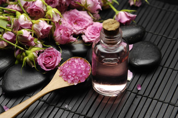 Branch rose with salt in bowl and massage oil on mat