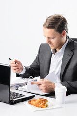 Hardworking man in suit with half eaten croissant