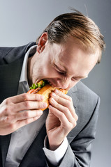 Man in suit eats BLT eagerly hungrily