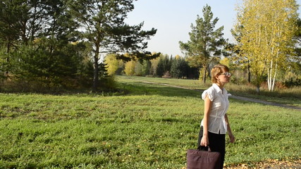 Businesswoman looking for the road in autumn park
