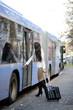 Dunkelhaarige Frau beim Einstieg in den Bus
