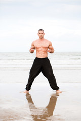 Man training exersises at the beach