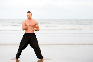 Man training karate at the beach