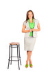 Young beautiful business woman stands near tall stool in studio