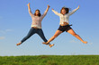 Two young fat girls jump at green grass at background of sky