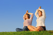 Two young girls meditate at green grass at background of sky