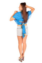 Back of beautiful woman dressed in shorts and blue pareo poses