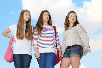 Three girls stand together at background of blue sky with clouds