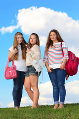 Three girls stand with bags on grass at background of blue sky.