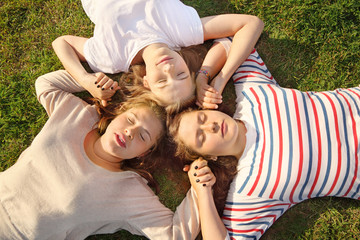 Three girls with closed eyes hold hands and lie on green grass.