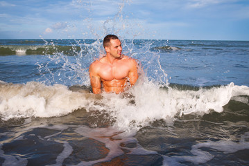 Young handsome muscular man at the sea
