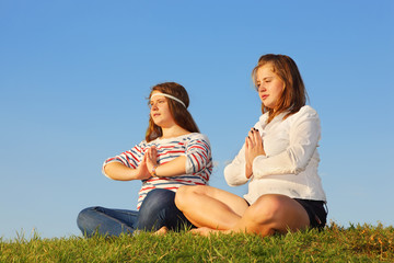 Two young girls meditate and reflect at green grass