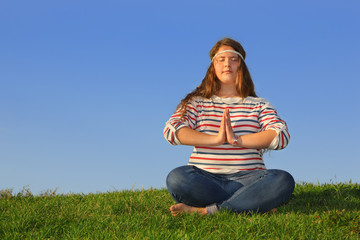 Fat girl in jeans sits at green grass and meditates