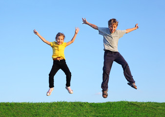 Boy and girl jump together at green grass at background of sky