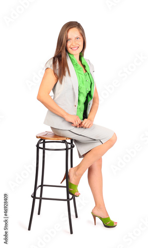 Young smiling business woman sits on stool in studio on white