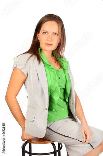 Young beautiful business woman sits on stool in studio on white