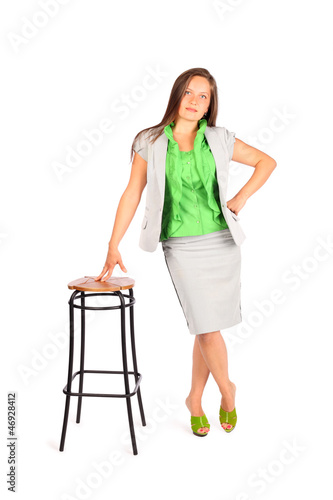 Young beautiful business woman stands leaning on tall stool