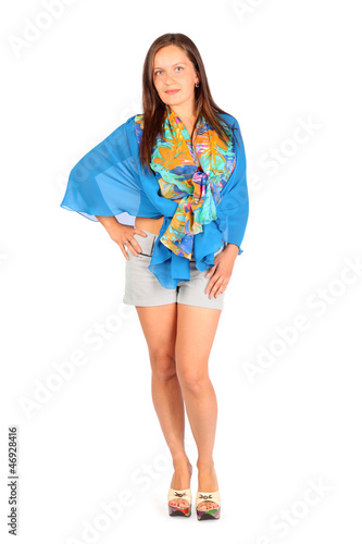 Beautiful woman dressed in shorts and blue pareo poses in studio