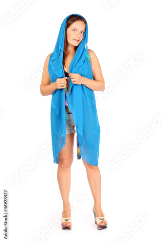 Smiling woman dressed in shorts and big blue scarf poses