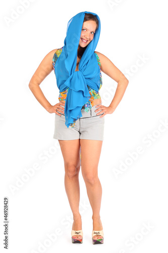 Happy woman dressed in shorts and blue pareo poses in studio