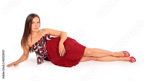 Beautiful young woman dressed in red pareo lies in studio