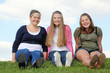 Three happy girls sit at green grass at background of sky