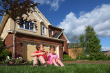 Little girl and boy with biscuits sits on grass near cottage