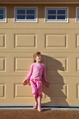 Little girl wearing in pink suit stands near yellow wall