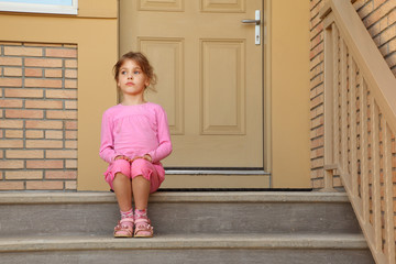 Little serious girl in pink suit sits on stairs near door