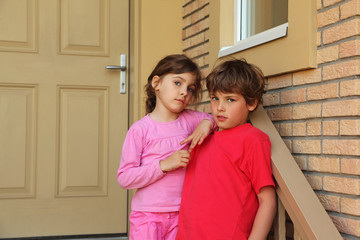 Brother and sister stand near door of cottage and look