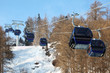 Ski chair-lift with skiers in forested mountains in  Alps