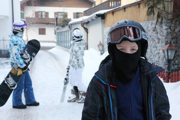 Boy wearing in sport suit and helmet stands in mountain village.