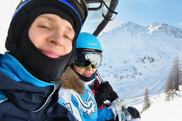 Male and female skiers in special clothing ride on cable car