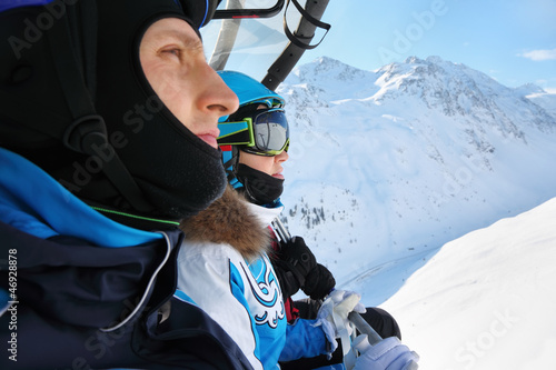 Male and female skiers in sport suits ride on cable car