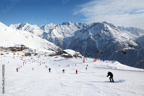 Cable car, buildings in mountains. Many skiers ride in Alps