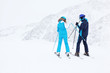 Woman and man skiers in suits and helmets prepare for slope