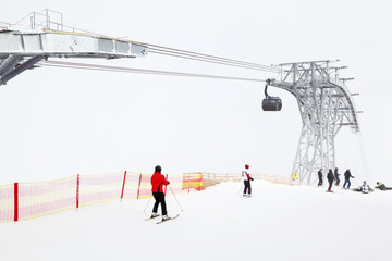 Big funicular in mountains. Skiers and snowboarders ride in Alps