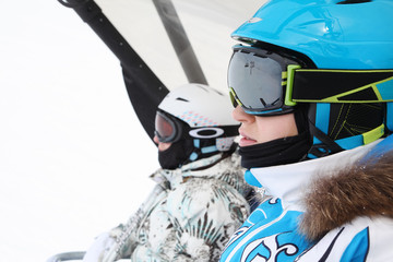 Two female skiers in special clothing ride on funicular