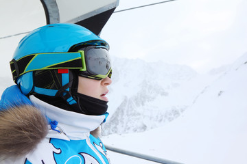 Rapt female skier in special clothing rides on funicular