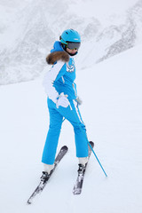Young woman skier in blue suit turns in winter