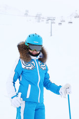 Smiling woman skier in suit and helmet looks at camera