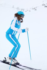 Smiling woman in blue suit and helmet skis at winter