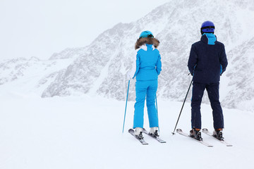 Woman and man skiers in suits and helmets look at slope