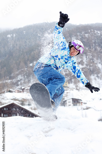 Smiling snowboarder jumps on snowboard on mountain
