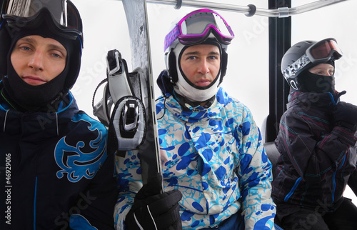 Three skiers in helmets ride on funicular in mountains.