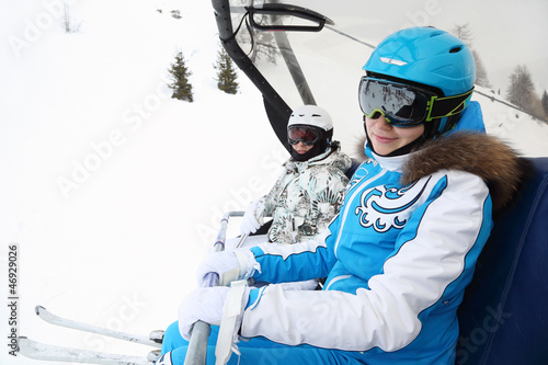 Two smiling female skiers in special clothing ride on cable car